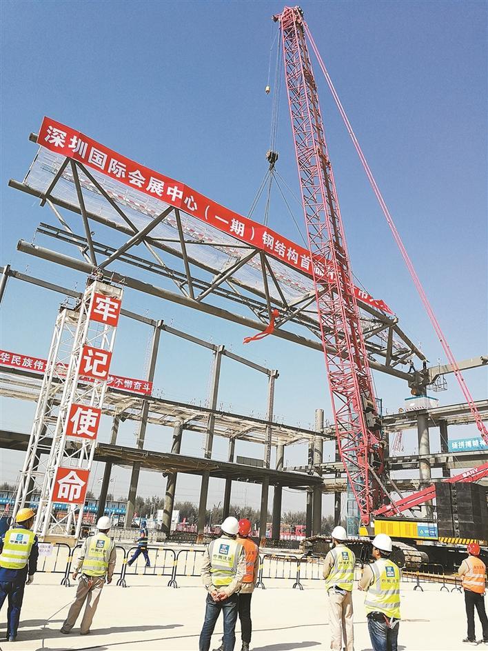 2017年12月22日上午,随着长47米、高7米、宽7米、重达84吨的首榀钢桁架(俗称房屋主梁)缓缓上升、平移、精准就位,全球规模最大的深圳国际会展中心正式进入钢结构主体屋面施工阶段!该项目于2017年9月21日开工,计划于2019年6月30日竣工,施工总工期648天。现场一片钢结构的森林,十九个标准展厅呈鱼骨式排布徐徐展开,蔚为壮观。 深圳国际会展中心项目地处粤港澳大湾区湾顶,珠三角广深澳核心发展走廊、东西向发展走廊、狮子洋与内伶仃洋交汇处的空港新城片区,是深圳市委市政府布局深圳空港新城两中心一馆的三